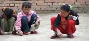 Doing homework - paper being an unneeded expense, girls practice their Chinese characters in the dirt.